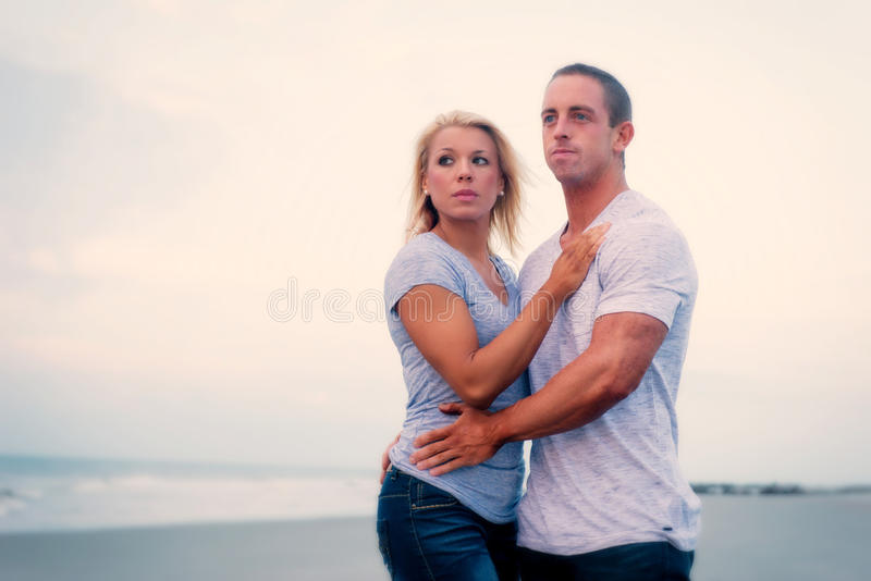 Young couple embracing on beach stock images