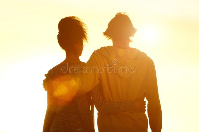 Young couple embracing looking at sunset stock images