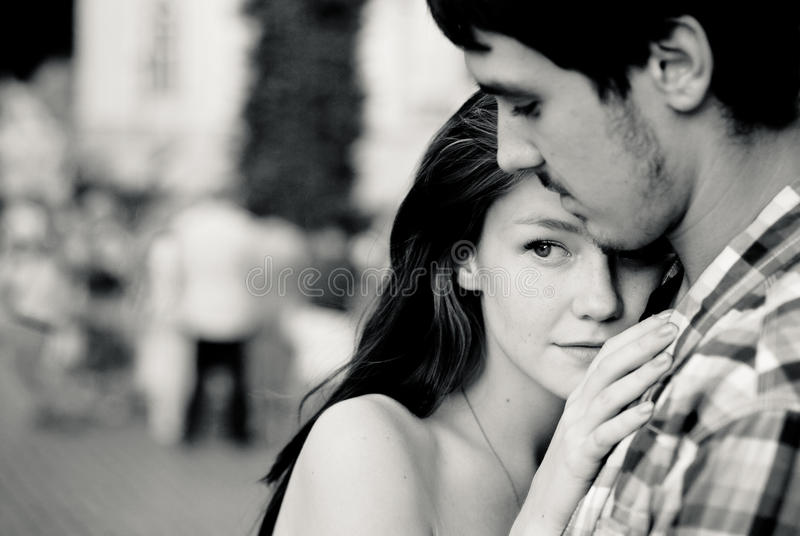 Young couple embracing tenderly in crowd royalty free stock photo
