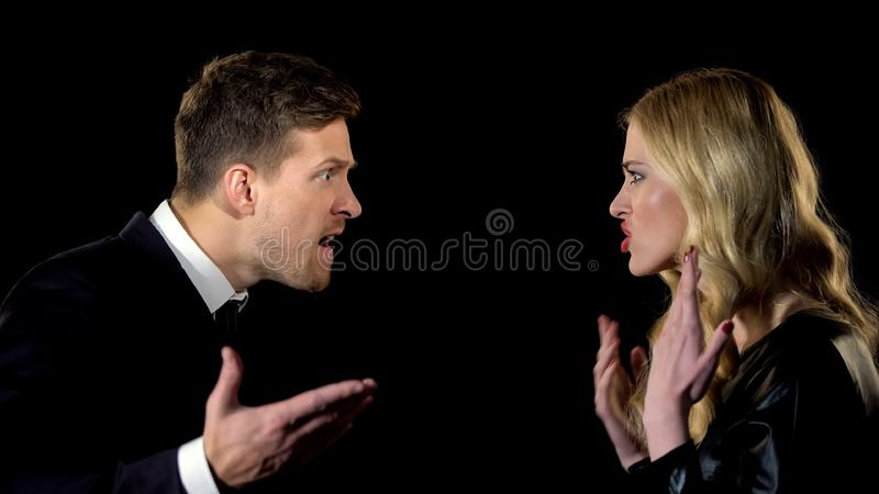 Young couple emotionally arguing against black background, misunderstanding stock image
