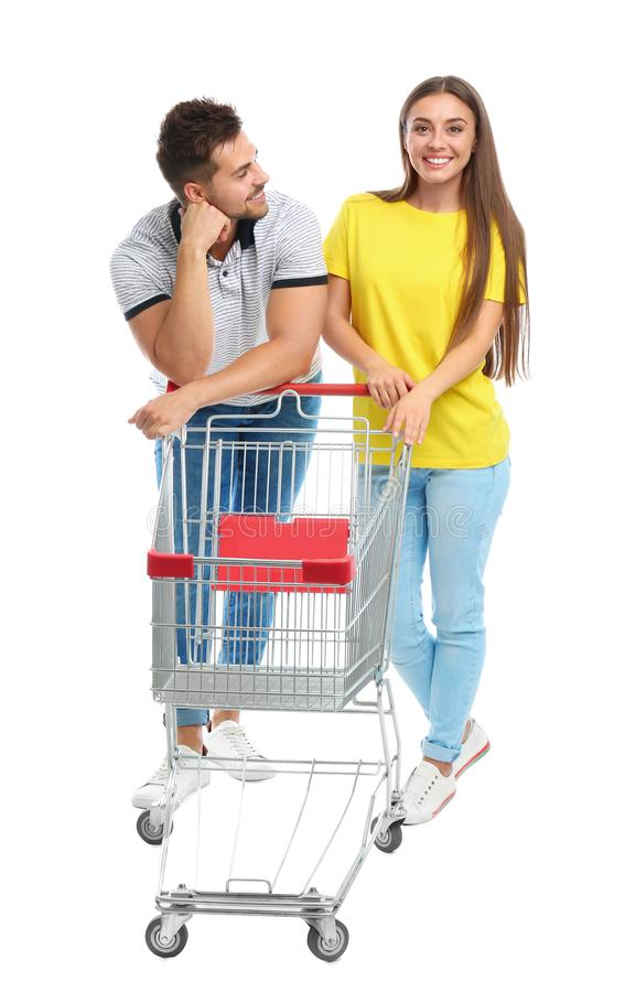 Young couple with empty shopping cart on background. Young couple with empty shopping cart on white background stock photos
