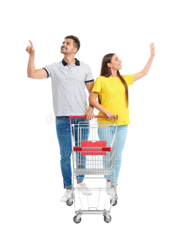 Young couple with empty shopping cart on background. Young couple with empty shopping cart on white background stock image