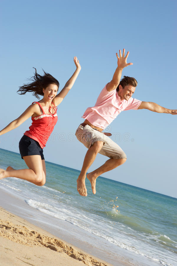 Young Couple Enjoying Beach Holiday Jumping stock images