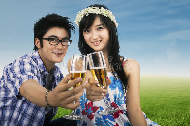Young couple enjoying champagne outdoor. Young happy smiling cheerful attractive couple celebrating with glasses of champagne, outdoor stock image