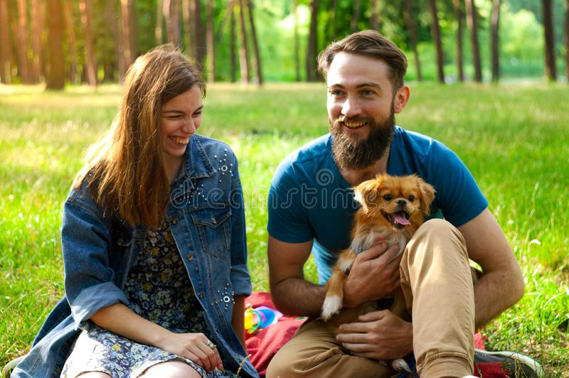 Young couple enjoying with a dog in a city park. royalty free stock photography