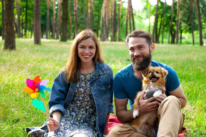 Young couple enjoying with a dog in a city park. royalty free stock image