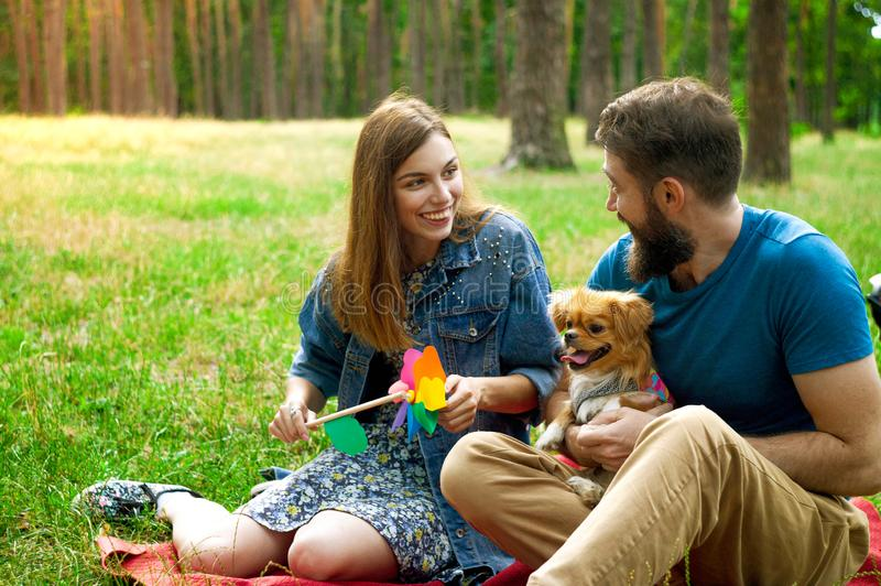 Young couple enjoying with a dog in a city park. stock images