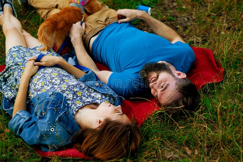 Young couple enjoying with a dog in a city park. stock image
