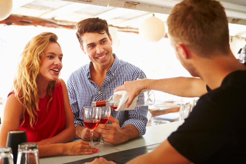 Young Couple Enjoying Drink At Outdoor Bar stock photos