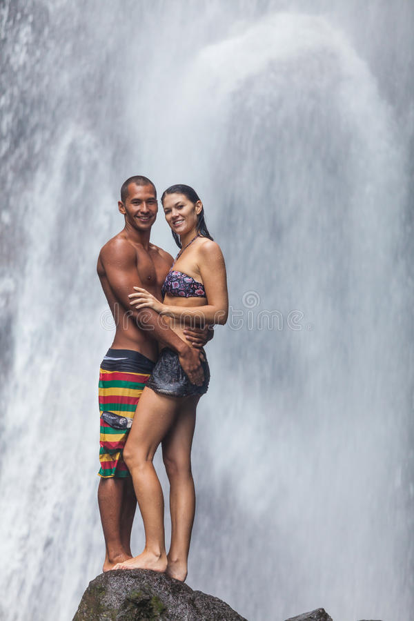 Couple at waterfall. Young couple enjoying the freshness of nature under a waterfall in the tropics royalty free stock photo