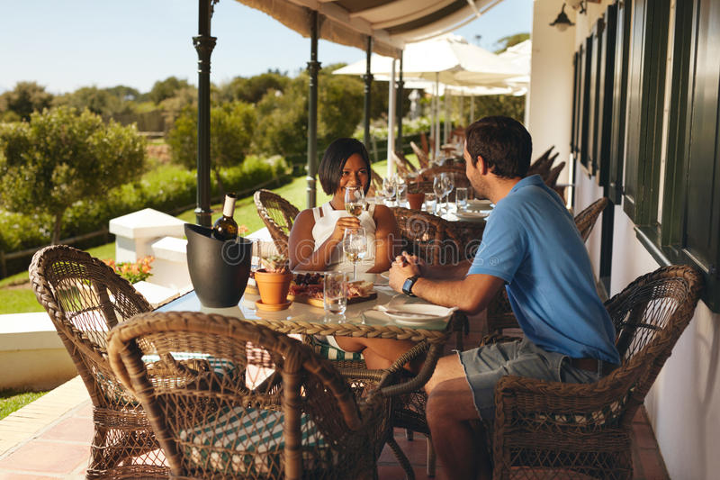 Young couple enjoying a glass of wine at winery restaurant royalty free stock photography