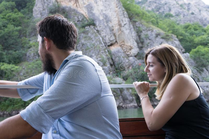 Young couple enjoying a journey sitting in a wood small boat looking to the water of the river. Blond girl and beard boy inside of stock photo