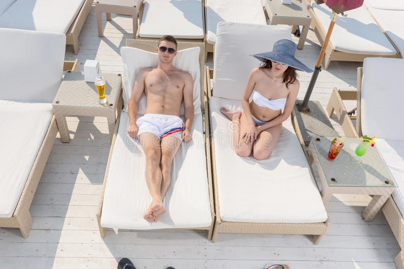 Young couple enjoying a lazy day in the sunshine. As they relax on recliner chairs at a seaside resort in the tropics on their summer vacation stock photography