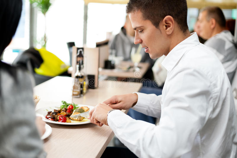 Young couple enjoying lunch at a restaurant royalty free stock photography