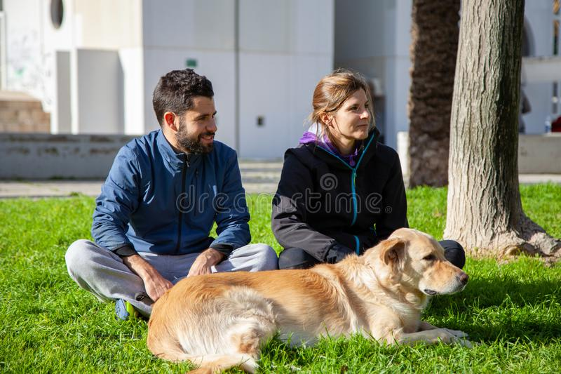 Young couple enjoying an outdoor park with their dog stock images