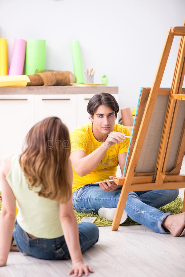 The young couple enjoying painting at home royalty free stock photos