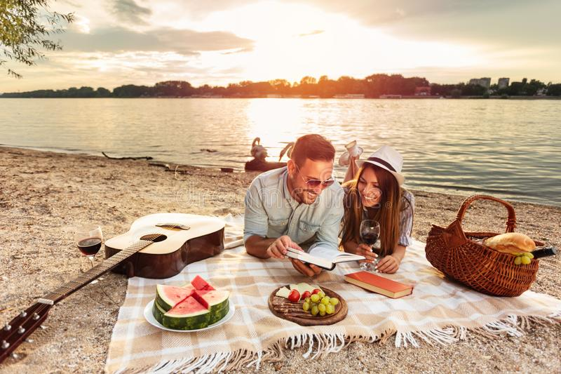 Young couple enjoying a picnic at the beach. Lying on the picnic blanket, reading books. White swans swimming and sunset over water in the background. Romance stock photos
