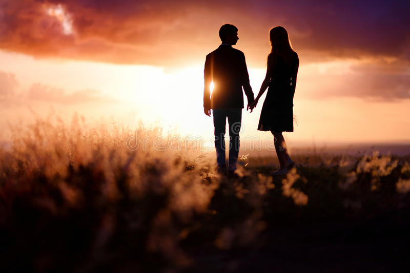 Young couple enjoying the sunset. In the meadow stock images