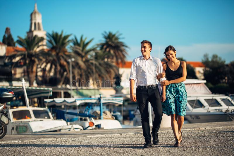 Young couple enjoying vacation time.Boyfriend and girlfriend having a romantic walk along the coast in a seaside town royalty free stock photos