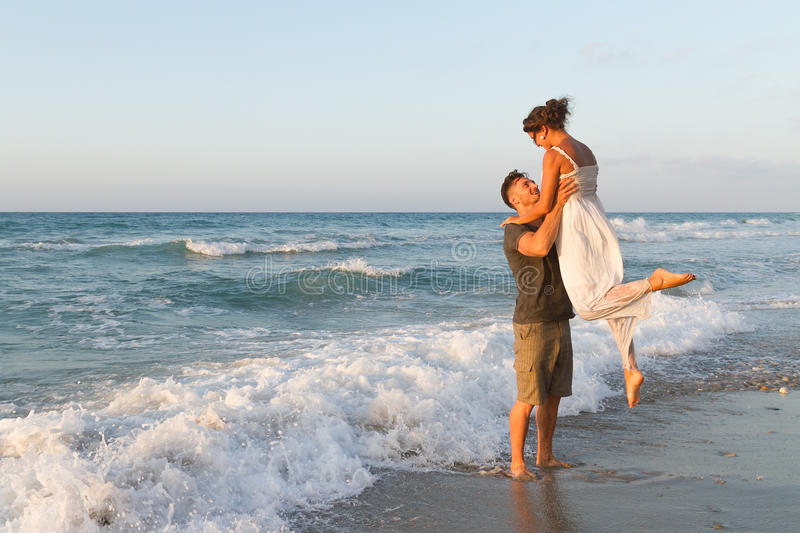 Young couple enjoys walking on a hazy beach at. Loving young couple at the beach , in a late summer hazy day at dusk, wearing a white dress and shorts, enjoying stock photos