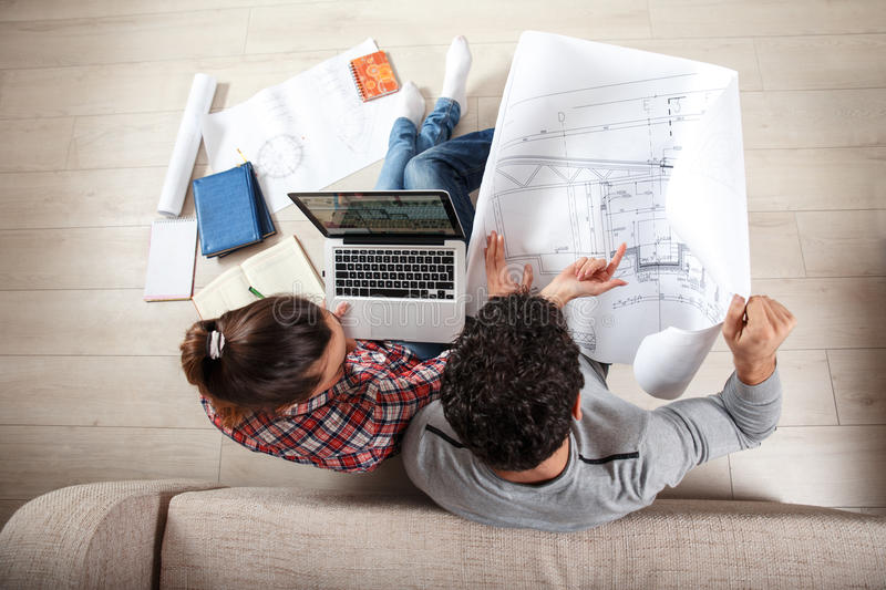Young couple examining blueprints royalty free stock photography