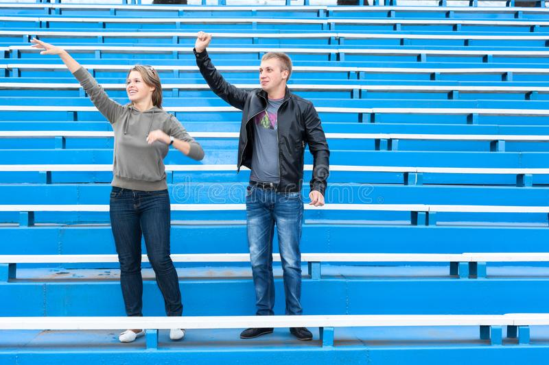 Young couple the fans cheer on team on empty stadium sector at match. Man and woman wave hands while standing together. Young couple the fans cheer on team on stock photos