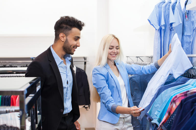Young Couple Fashion Shop, Happy Smiling Man And Woman Customers Choosing Clothes Formal Wear Shopping royalty free stock images