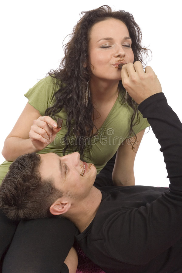 Young couple feeding each other chocolate. (white background stock photo