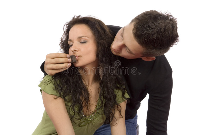 Young couple feeding each other chocolate. (white background royalty free stock images