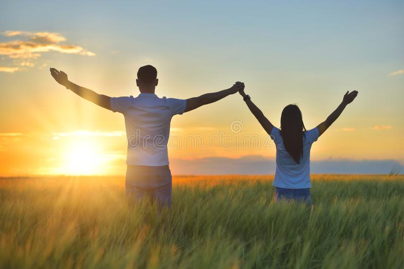 Young couple feeling free in a beautiful natural setting, in what field at sunset royalty free stock photography