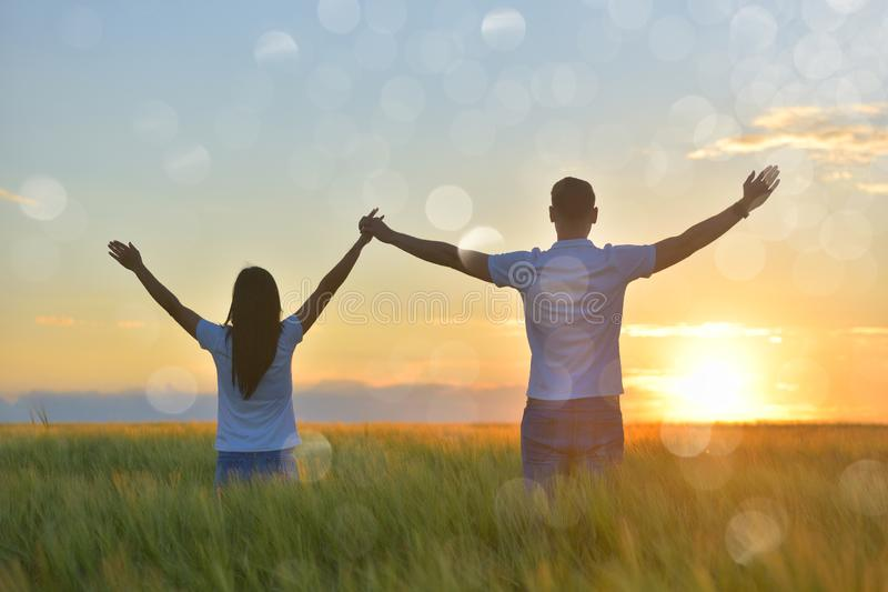 Young couple feeling free in a beautiful natural setting, in what field at sunset stock photo