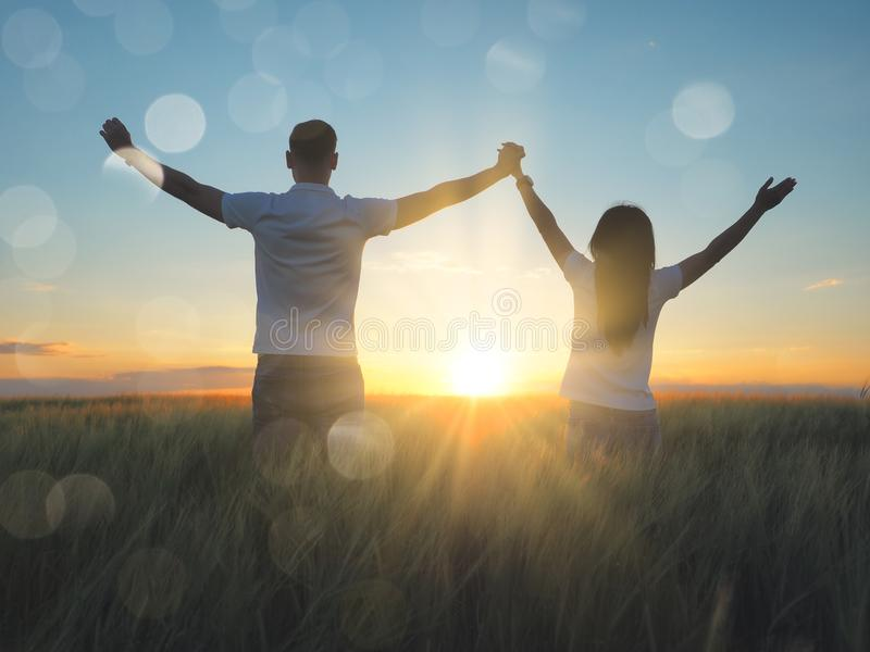 Young couple feeling free in a beautiful natural setting, in what field at sunset royalty free stock image