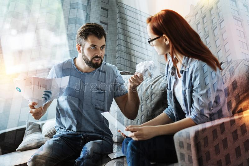 Young couple feeling furious while having a quarrel. Quarrel. Emotional young expressive men feeling furious and scrunching documents in his fists when shouting stock photos