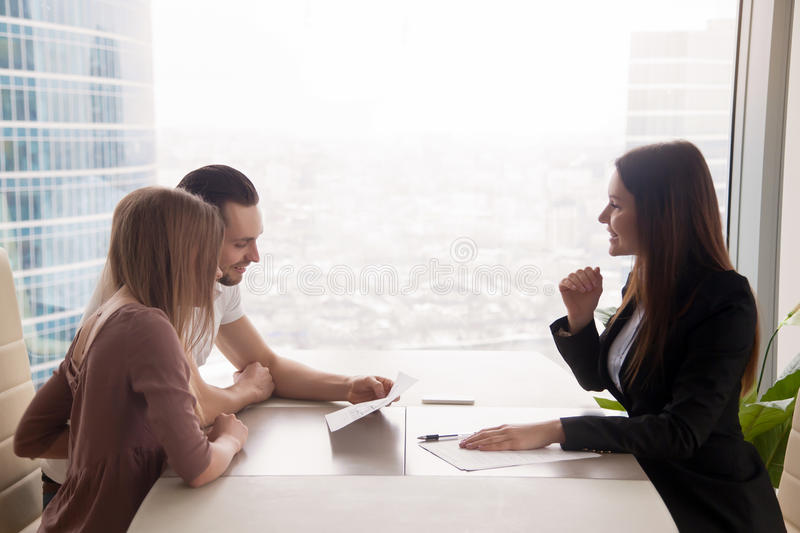 Young couple and female estate broker discussing property for sa. Side view of realtor and young couple sitting at office desk discussing property for sale royalty free stock photography