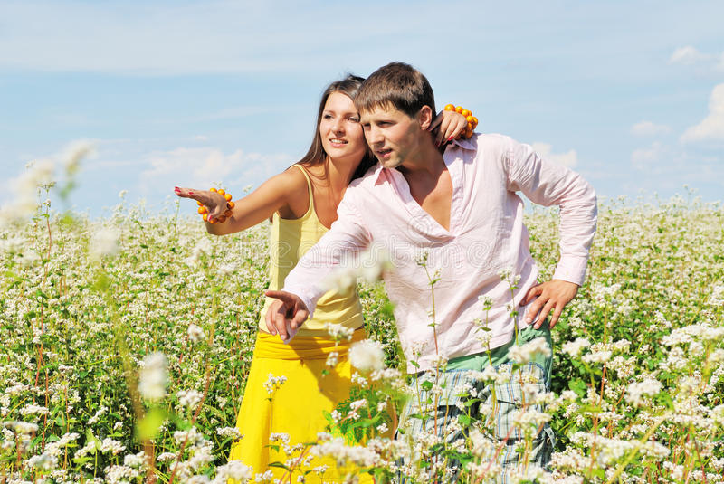 Young couple on field of flowers pointing. Young couple on field of flowers in sunny day stock images