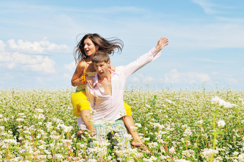 Young couple on field with fresh flowers. Young couple on field of flowers royalty free stock photos
