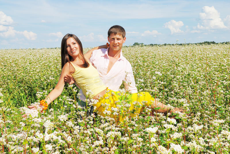 Young couple on field with fresh flowers. Young couple on field of flowers royalty free stock images