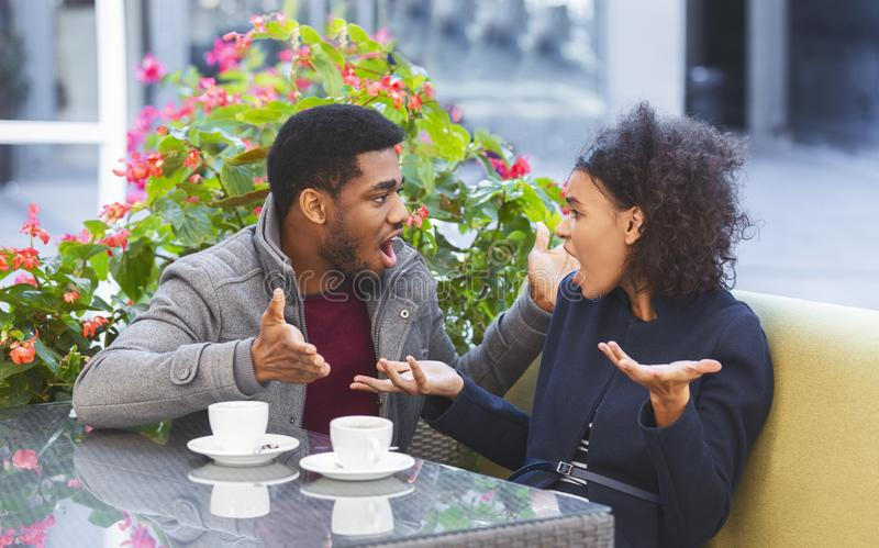 Young couple fighting while dating at cafe. Young african couple fighting while dating at cafe, shouting at each other, panorama with copy space stock photo