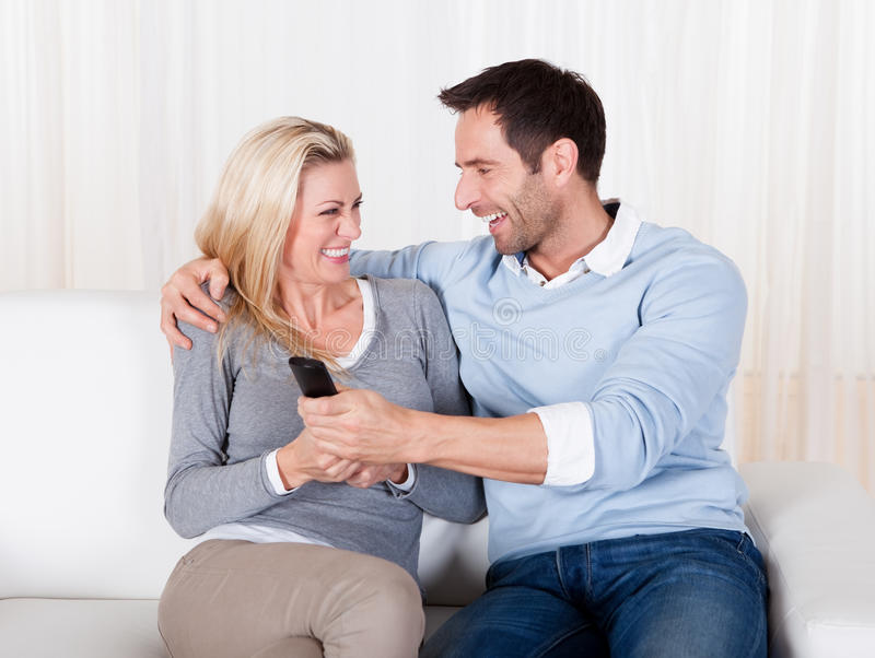 Young couple fighting for TV remote stock photos