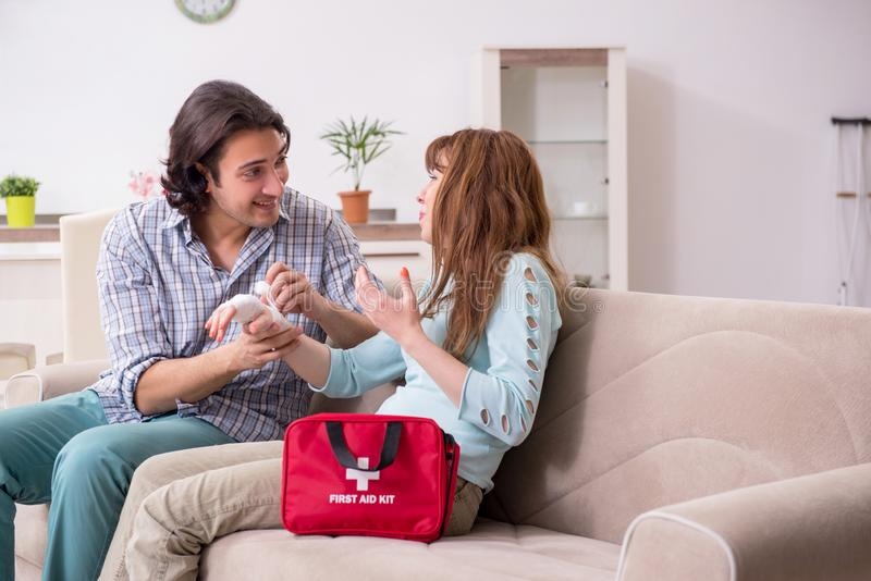 Young couple in first aid concept at home. The young couple in first aid concept at home royalty free stock image