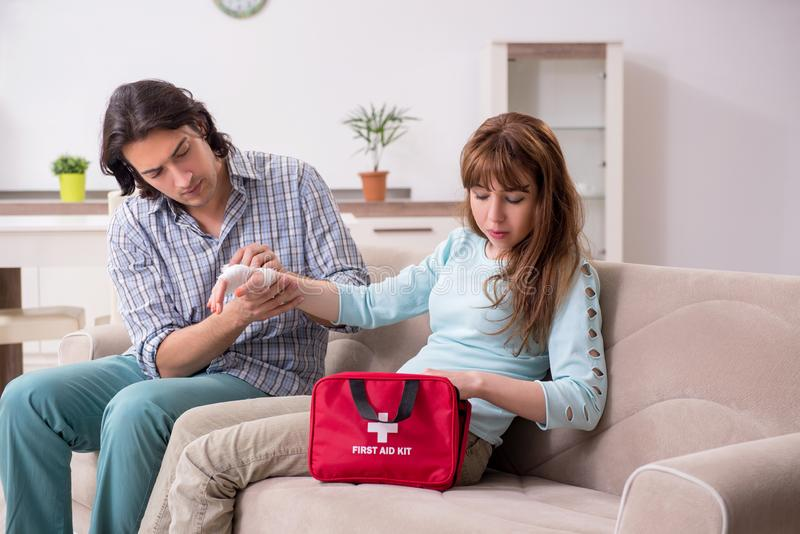 Young couple in first aid concept at home royalty free stock photography