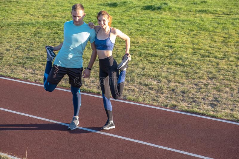 Young couple of fit sportsmen boy and girl doing warming up exercises  before running on red tracks of public stadium outdoors.  royalty free stock images