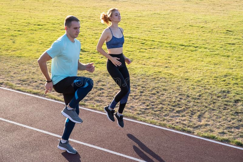 Young couple of fit sportsmen boy and girl running while doing exercise on red tracks of public stadium outdoors royalty free stock photography