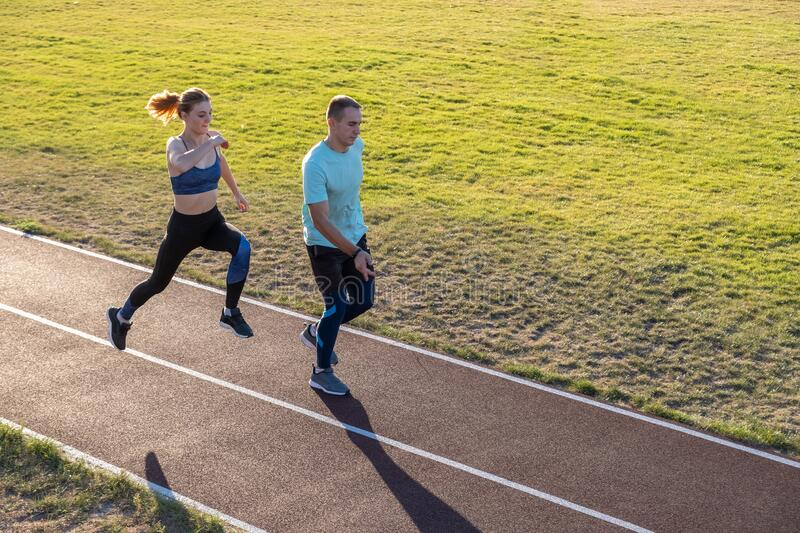 Young couple of fit sportsmen boy and girl running while doing exercise on red tracks of public stadium outdoors.  stock photo