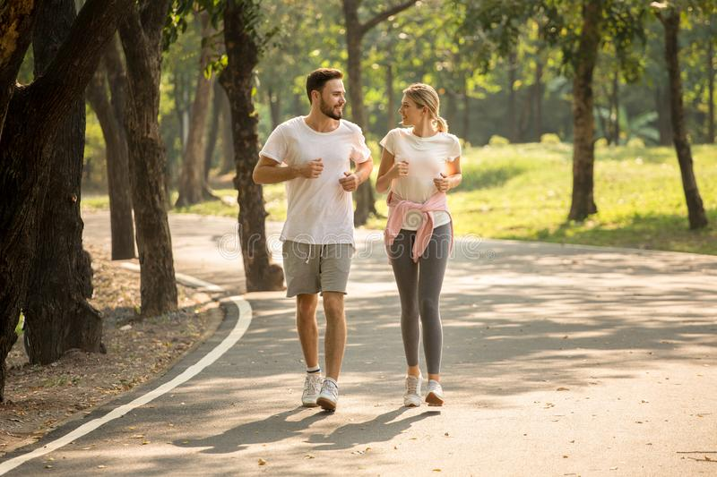 young couple fitness in sportswear running together in park . sport man and woman jogging outdoors in nature. workout ,exercising royalty free stock image