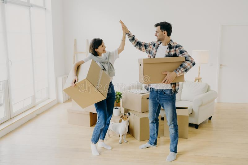 Young couple five high five to each other, carry big cardboard boxes during moving day, agree to work as team, pose in new stock image