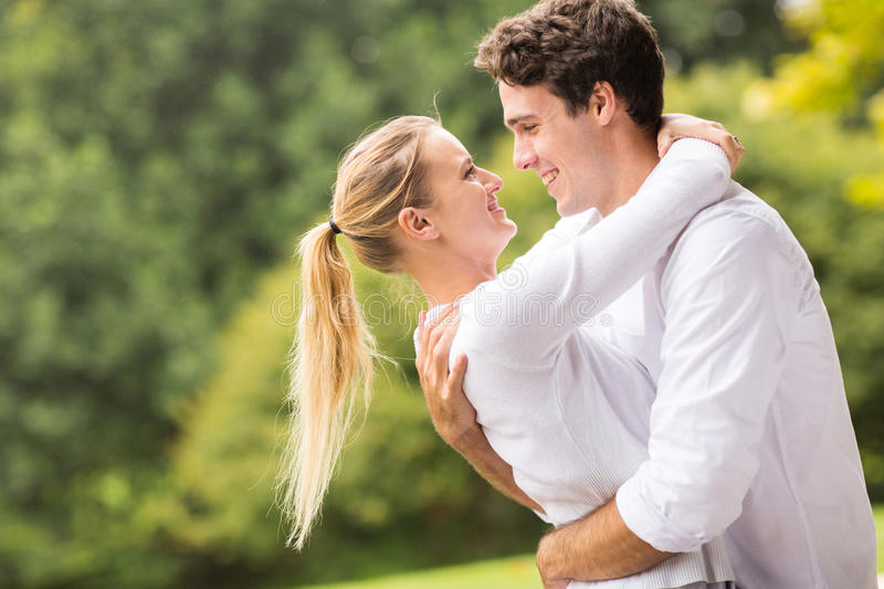 Young couple flirting. Intimate young couple flirting outdoors stock photo