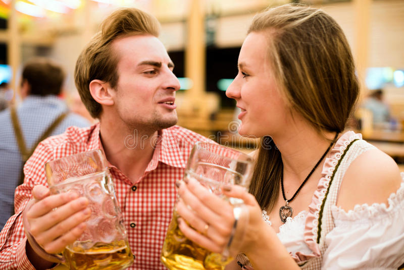 Young couple flirting in Oktoberfest beer tent royalty free stock photo