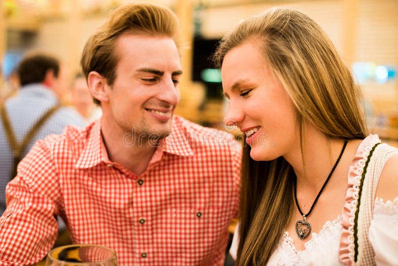 Young couple flirting in Oktoberfest beer tent. Young couple in traditional Bavarian Tracht - Dirndl and Lederhosen - in a beer tent at the Oktoberfest enjoying stock images