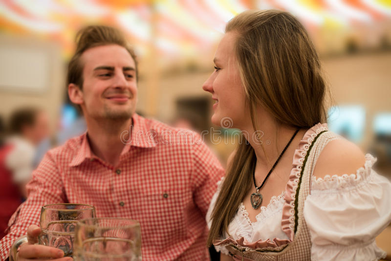 Young couple flirting in Oktoberfest beer tent stock image